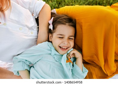 Closeup image of happy child playing with her mother, enjoying the time together. Cute little girl laughing with mom sitting on the grass in the park. Mother and daughter shares love. Mothers day