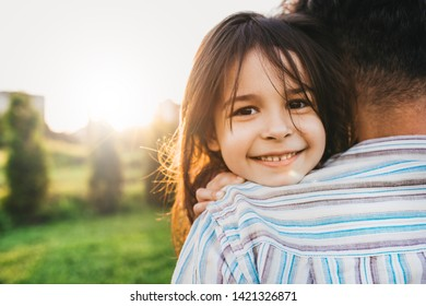 Closeup image of happy daughter embraces her dad feels joyful. Happy cute little girl playing with father in the park, smiling and looking to the camera. Father's Day. Daddy and daughter shares love.