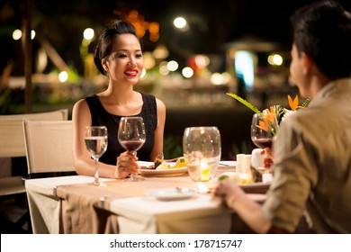 Closeup image of a happy young woman at a date with her boyfriend on the foreground