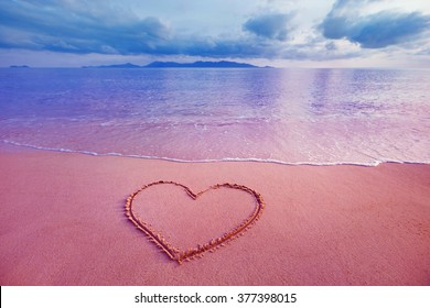 Closeup image of heart symbol written on sand at pink sea sunrise background.