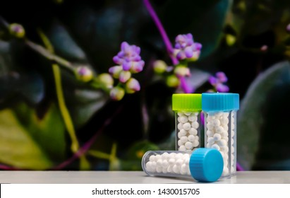 Closeup image of homeopathic medicine consisting of the pills bottle with blurred purple flowers and green leaves background.