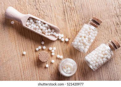Closeup image of homeopathic medicine consisting of the pills and a bottle containing a liquid homeopathic substance.