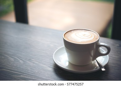 Closeup image of hot Latte coffee cup on vintage wooden table in cafe