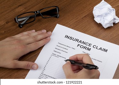 Close-up image of a human hand about to fill up the blank insurance claim form