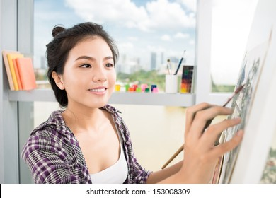 Close-up image of a lovely artist busy with painting on the foreground