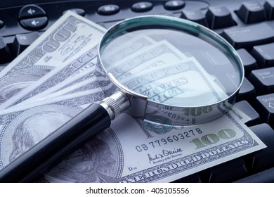 Closeup image of magnifying glass on computer keyboard with hundred dollar bills. Selective focus.