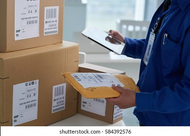 Close-up image of mail worker checking information on parcels