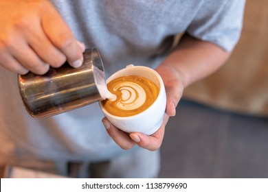 Closeup image of male barista's hands holding and pouring milk for prepare cup of coffee, latte art, Concept for coffee preparation and service. the image focus on pouring milk and coffee.