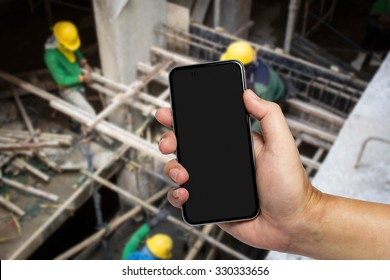 Closeup image with male hand hold and touch screen smart phone, tablet,cellphone over blurred Construction site background.