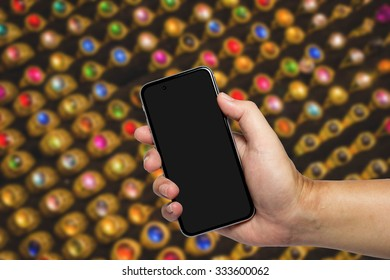 Closeup image with male hand hold and touch screen smart phone, tablet,cellphone over blurred night Market background.