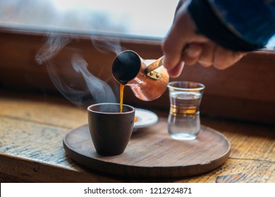 Closeup image of male hand pouring coffee in a vintage cup. First morning coffee preparation