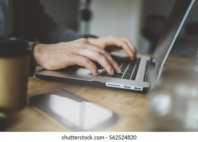 Close-up image of male hands typing on laptop keyboard, smartphone on the table, professional manager using portable computer at office, technology and business concept