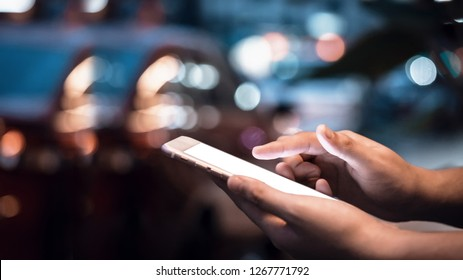 Close-up image of male hands using smartphone at night on city shopping street, searching or social networks concept, hipster man typing an sms message to his friends