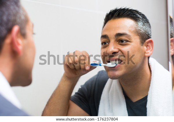 Closeup image of a man brushing his teeth while looking in the mirror in the apartment on the foreground