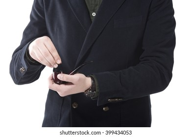 Closeup image of man filling up tobacco in pipe
