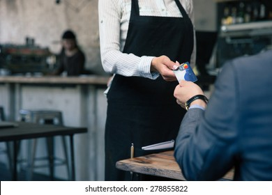 Closeup image of a man giving credit card to waiter in cafe