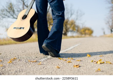 Closeup image of man musician walking with guitar in hand on autumn highway covered with yellow leaves copyspace background