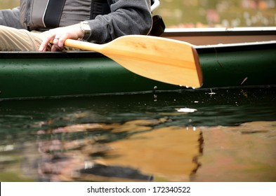 close-up image of a man on a river in a green canoe with a wooden paddle
