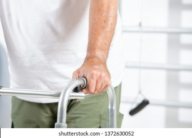 Closeup image of man using a walker to assist with rehabilitation