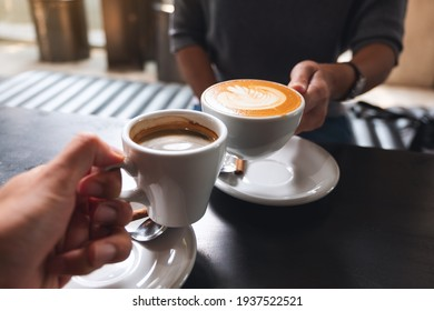 Closeup image of a man and a woman clinking white coffee mugs in cafe