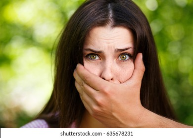 Closeup image of a man's hand covering a scared woman's mouth. Domestic violence, abuse, kidnapping concept.