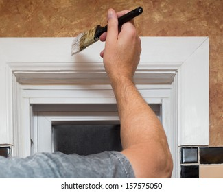 Closeup image of a mans hand with paintbrush while painting window trim