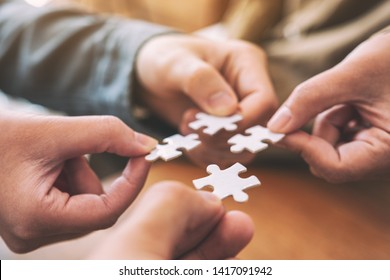 Closeup image of many people hands holding and putting a piece of white jigsaw puzzle together