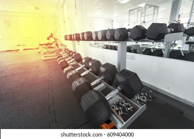 Closeup image of a modern gym interior with equipment. Rows of dumbbells in the gym.