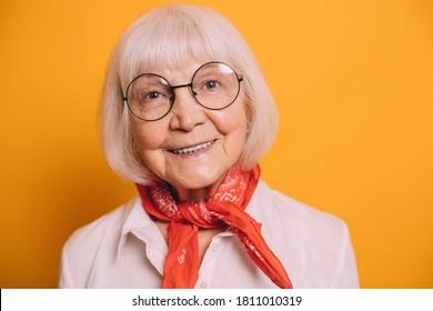 Nahaufnahme einer alten, fröhlichen Frau mit weißem Haar und grauen Augen, die runde Brille trägt, weiße Bluse, orangefarbener Schal oder Krabbe. Frau einzeln auf orangefarbenem Hintergrund und lächelnd