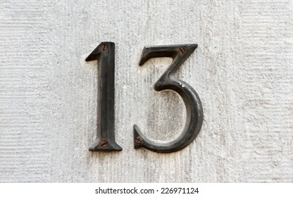Closeup image of an old rusted metal number 13 on a gray wall