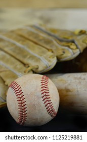 Closeup image of old and used baseball, mitt or glove and bat on dark table with wooden background. Shallow depth of field