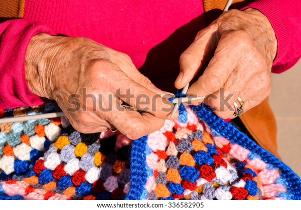 Close-up image of an old woman with knitting needles and wool