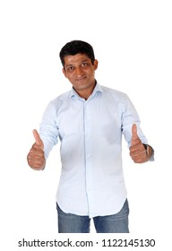 A closeup image on an East Indian man in jeans and blue shirt standing