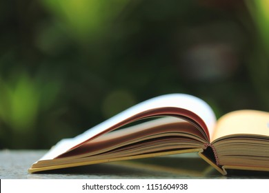 Close-up image of open book on the floor. Colorful lights are the background selective focus and shallow depth of field