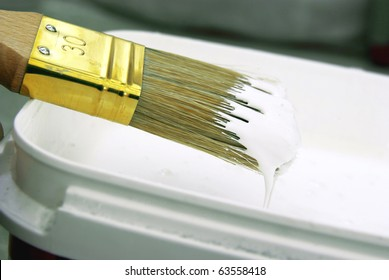 Close-up image of a paint brush with white paint.