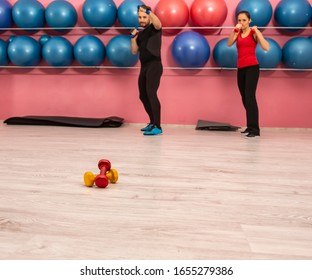 Close-up image of a pair of dumbbells on the floor in a gym.
