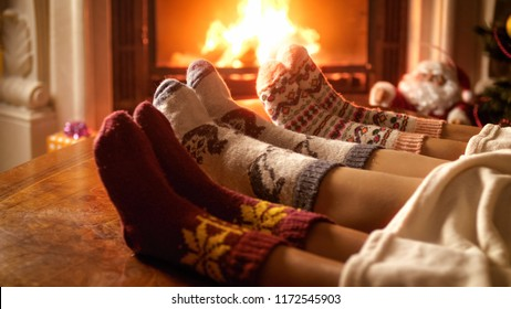 Closeup image of parents with child in woolen socks warming at night by the fireplace