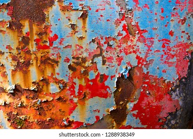 Close-up Image of Peeling Paint and Rust on the Door of an Old Junk Car