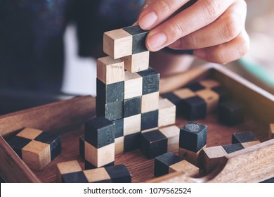 Closeup image of people playing and building wooden puzzle game