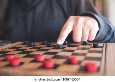 d79d1b4663aed Closeup image of people playing and moving checkers in a chessboard