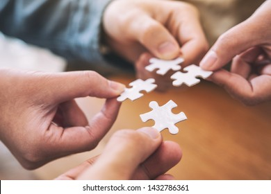 Closeup image of people's hands holding and putting a piece of white jigsaw puzzle together