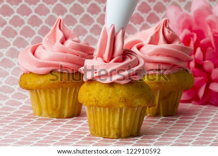 Close-up image of a person decorating cupcakes with an icing tube.