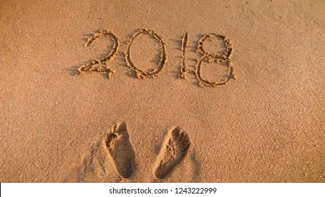 Closeup image of person's footprints and 2018 New Year number written on sea beach sand. Perfect image to illustrate Christmas, winter holidays, travel and tourism.