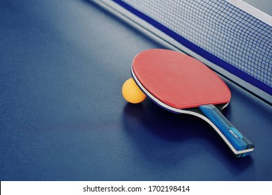 Close-up image of ping-pong racket and orange ball ion table with net