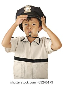 Closeup image of a preschooler blowing a whistle while adjusting his policeman's hat.