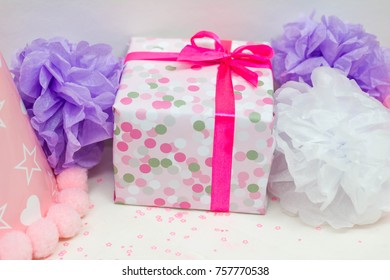 Closeup image of present and tissue pompoms for kid's birthday p