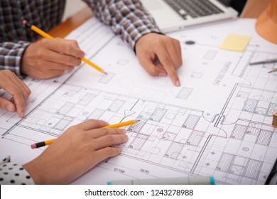 Close-up image of professional engineers discussing construction plan at meeting
