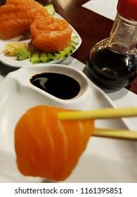 Close-up image of raw salmon slice or salmon sashimi insured with hashi and background soy sauce and sliced sashimi image decorated with cucumber, ginger, wasabi