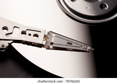 A close-up image of the read & write head of an Hard Disc Drive against the platter. / THE HDD