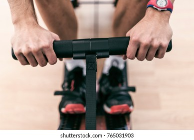Close-up image of rowing athlete hands in gym exercise machine